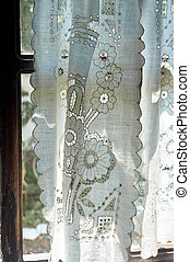A window in a whitewashed hut with a wooden frame, a Lacy linen starched curtain. The interior of the house. Ukraine, the Cossacks