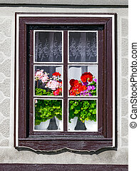 A window outside the house with blooming geranium flowers in an old European house