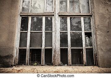 A window with a broken window pane. Broken glass.