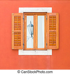 A window with a reflection of an ancient street lamp with wooden shutters on the red wall of the house.