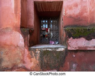 A window with an ancient metal lattice on a red wall in the medina of Marrakesh, Morocco.