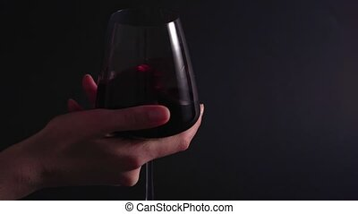 A wine expert rotates and tests a glass of drink at a winery. The final process of making alcohol. Isolated, static shot, black background