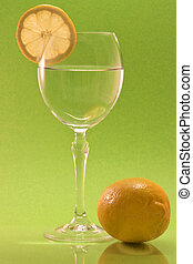 A wine glass with a lemon slice and a whole lemon in front and a green background