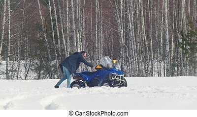 A winter forest. A man tries to get the snowmobile out of...