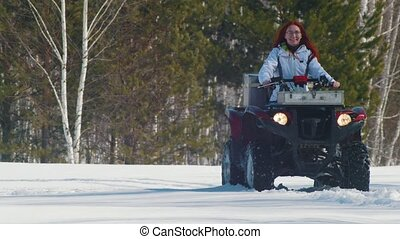 A winter forest. A woman with ginger hair riding big red...