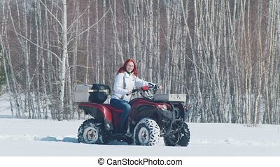 A winter forest. A woman with ginger hair riding snowmobile...