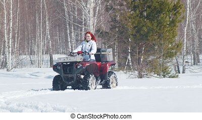 A winter forest. A woman with ginger hair riding snowmobile....