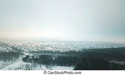 A winter forest and a village in the distance. An overview...