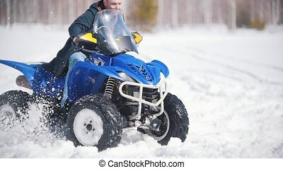 A winter forest in daylight. A man riding a big snowmobile....