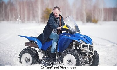 A winter forest in daylight. An adult man riding a big...