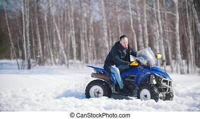 A winter forest in daylight. Cold weather. A man riding a...