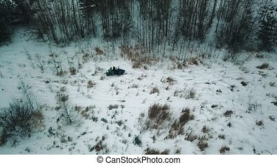 A winter forest. Two people riding the snowmobile. Wide shot