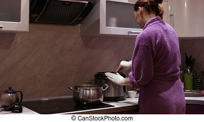 A woman adds to the saucepan sour cream dollop - A housewife...