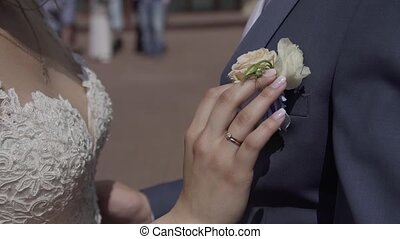 A woman adjusts a buttonhole for a man