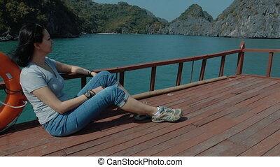 A woman admires the beautiful views of Ha Long Bay.