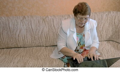 A woman aged, working on a laptop at home