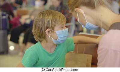 A woman and a boy both wearing medical facemasks are at the airport. A woman applies hand sanitizer on the boy's hands. The concept of the New normal of people's lifestyle. Air travel in the age of Covid-19.