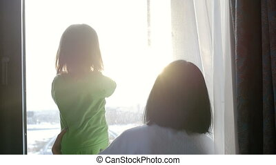 A woman and a child are looking out the window and playing with the sun. Love in the family.