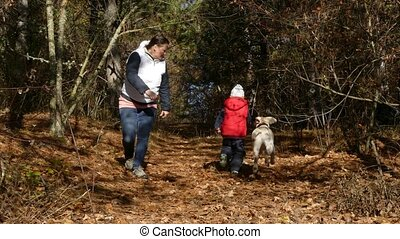 A woman and a child are playing with a dog in the forest.