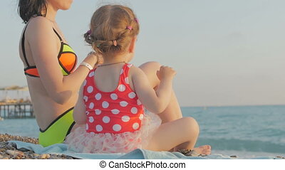A woman and a girl are sitting on a beautiful beach and throw stones at sea. The concept of family, love, happiness, recreation and holiday.