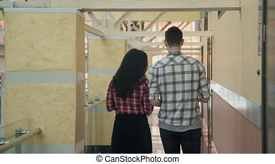 A woman and a man talking and slowly go the distance hall corridor.