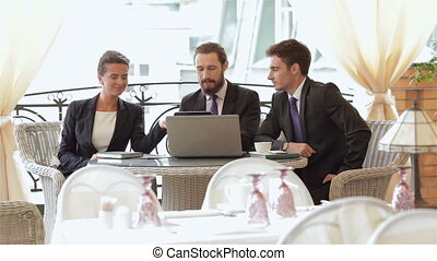 A woman and a two man on a business lunch in a restaurant. Smiling attractive businesswoman and man having discussion. While drinking coffee at lunch break. Businesspeople having business lunch outside on the terrace in a fine dining restaurant.