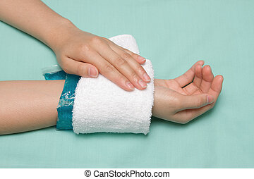 a woman applying cold pack on swollen hurting wrist after...