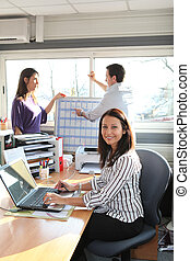 a woman at work with colleagues