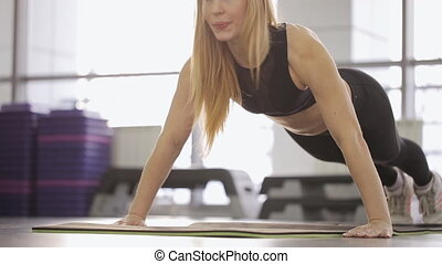 A woman athlete is pushed from the floor. building muscles in front delts shoulder in the gym