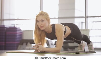 A woman athlete performs a plank in the gym. Load abdominal muscles, back.