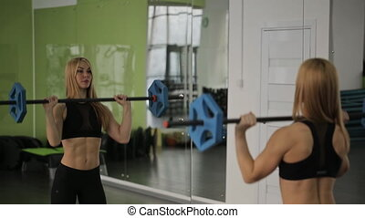 A woman athlete using the barbell with weights, trains on the shoulders and triceps in the gym.