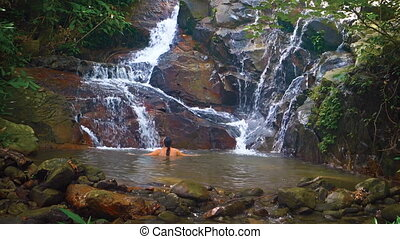 A woman bathes in the natural tropical waterfall