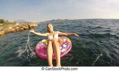 A woman bathes in the sea with a pink circle.