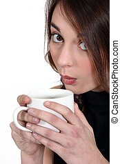 A woman blowing on her drink.
