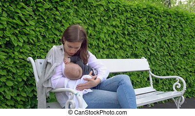 A Woman Breastfeeding her Child in the Park