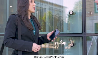 A woman business executive shows her male colleague something on her smart phone