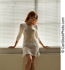 A woman by the window at home