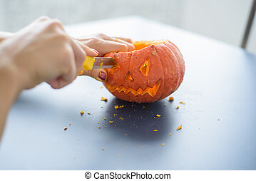 A woman carves her face on a pumpkin for a Halloween lamp on a black table. Close-up female hands making Jack-o'-lantern to the eve of all saints.