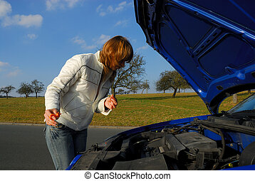 A Woman Checking the Motor Oil in Her Car