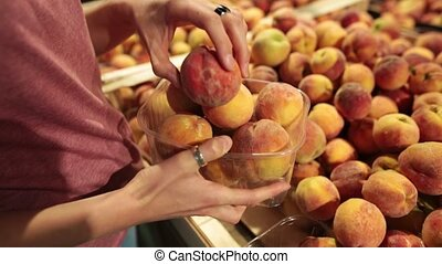 A woman chooses peaches on the store counter. She puts the peaches in a plastic box.