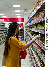 A woman chooses pickled vegetables at the grocery store