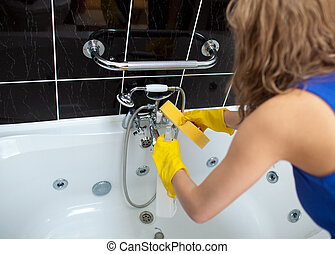 A woman cleaning a bathroom with a sponge