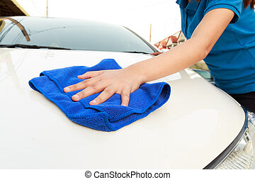 A woman cleaning car with microfiber cloth