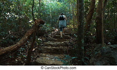 A woman climbs up a steep steps