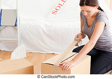 A woman closing a cardboard with tape