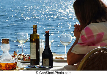 a woman consumes food. at the background the sea