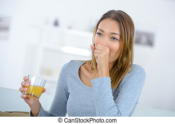 a woman coughing drinking juice