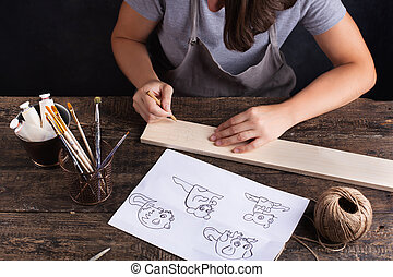 A woman creates future drawing of a Christmas tree toy. Gray background. Symbol of the new year rat.