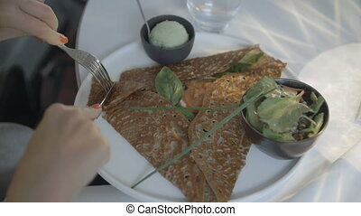A woman cutting through a crepe - A POV close up shot of a...