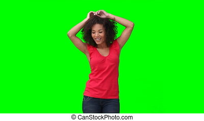 A woman dancing against a green background